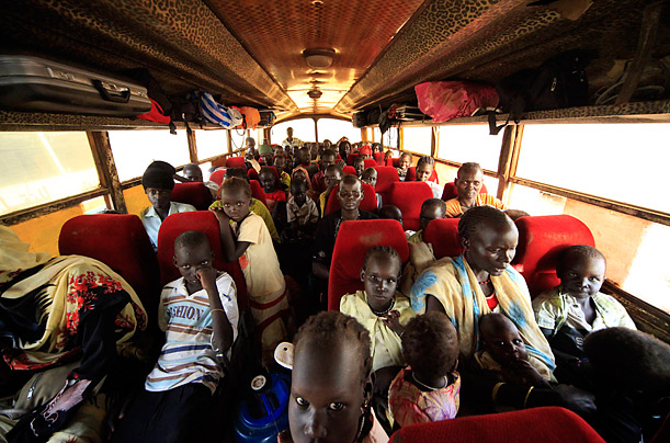 A group of internally displaced people sit in a bus in a transport convoy bound for Unity state in south Sudan.