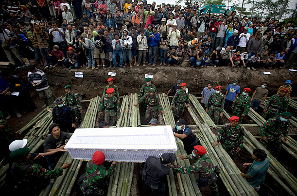 Indonesian soldiers and volunteers carry the coffin a victim of the Mount Merapi eruption during mass burial near Yogyakarta, Indonesia.