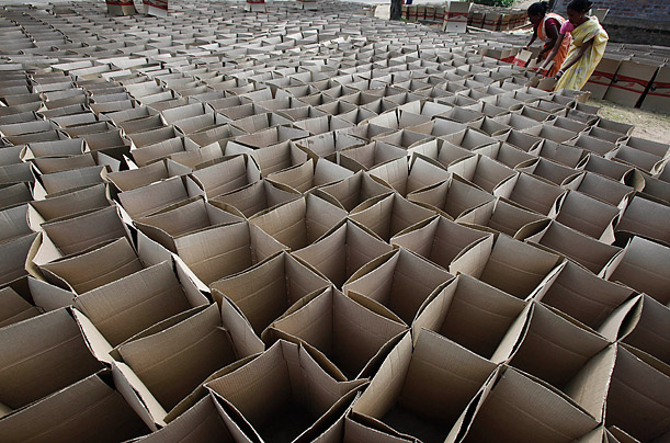 Indian laborers make cartons in Bonda, India.