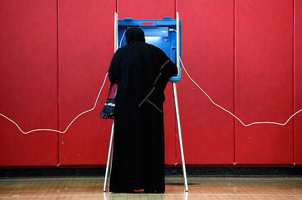 Tahani Ahmed fills out her ballot while voting at Lowrey School in Dearborn, Michigan.