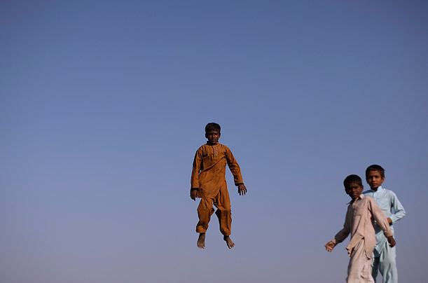 Boys displaced by this summer's massive flooding in Pakistan play on a trampoline next to their camp in Basira village, Punjab Province.