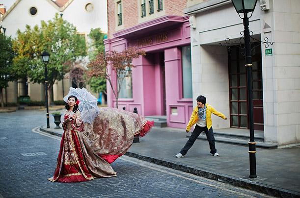 A Chinese newlywed poses for a wedding photograph in Songjiang, China. Chinese couples gather daily to have their wedding portraits taken in the themed town.