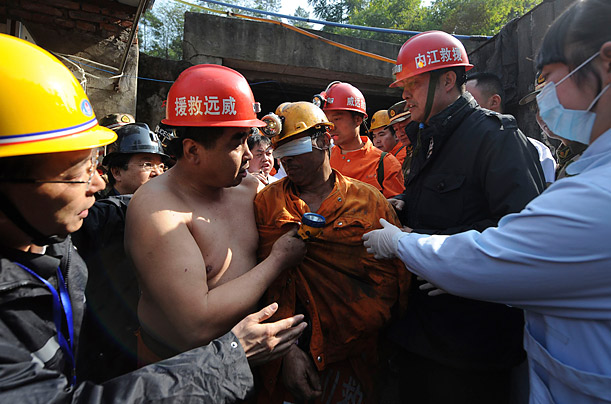 Liu Mingquan (C) arrives back on the surface after a flood trapped 29 coal miners in southwestern China. Rescuers were able to save all the workers.
