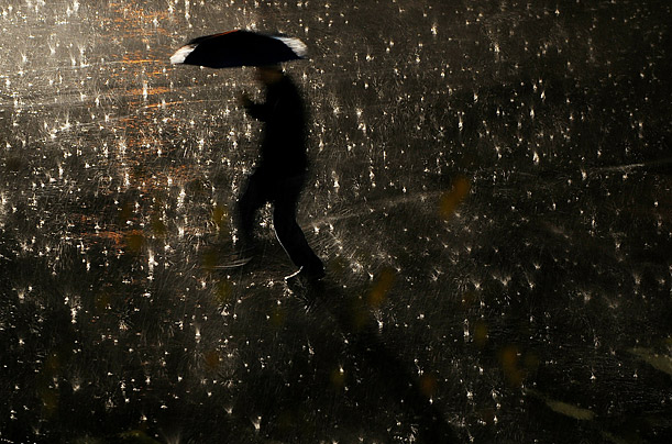 A man walks with his umbrella during a heavy rain in Pristina, Kosovo.