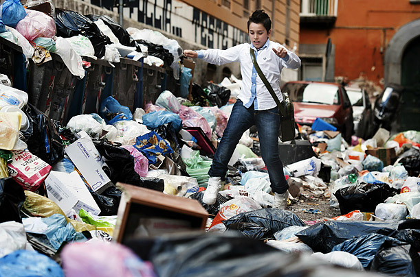 A child walks through piles of garbage in the streets of Naples, Italy. The accumulated waste in the city was likely to reach 3,600 tons by the end of the day.