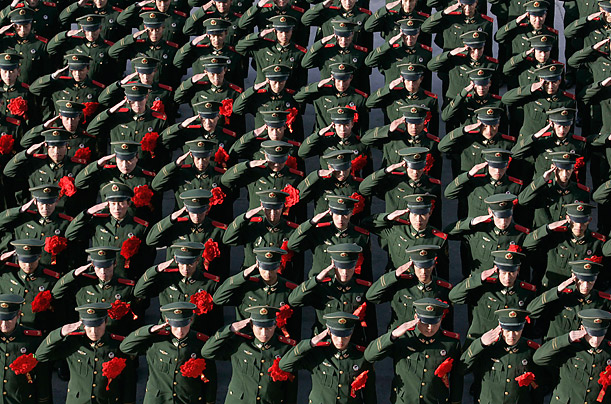Retiring paramilitary policemen salute during a ceremony at an army base in Taiyuan, China.