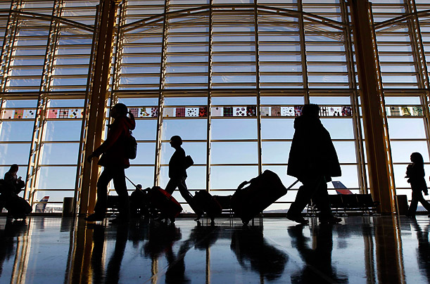 Travelers walk through the terminal at Washington's Ronald Reagan Washington National Airport as they holiday travel season began.