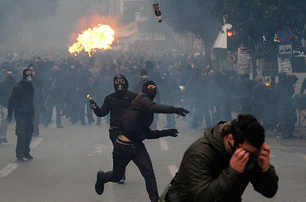 Protesters throw petrol bombs during clashes in Athens.  20,000 people marched to parliament during a general strike against a new round of labor reforms in the crisis-hit country.
