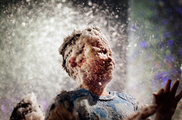 Children's faces are covered with foam used to simulate snow at a shopping mall in Singapore where malls are taking advantage of the festive season to draw in customers through visual