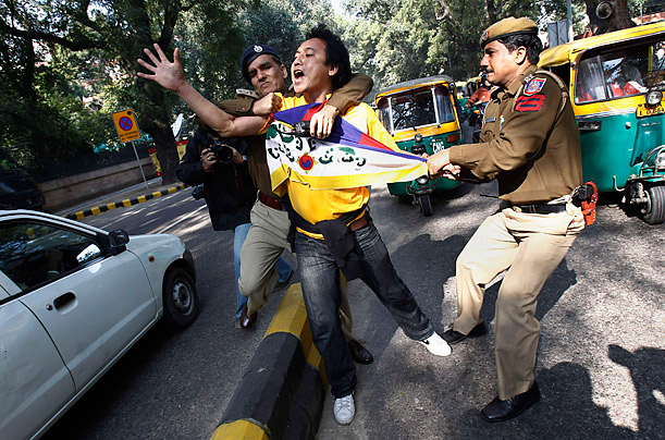 Police officers detain a Tibetan exile during a protest outside the venue of the India-China joint meeting in New Delhi. Yesterday China and India struck business deals worth over $16 billion.