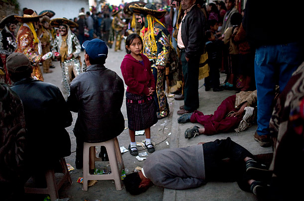 A girl stands next to two men passed out drunk during celebrations commemorating Santo Tomas in Chichicastenango, Guatemala.