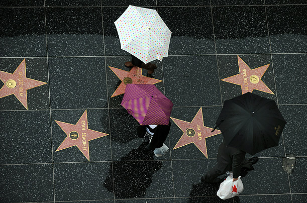 Pedestrians walk under the rain on the Hollywood Walk of Fame in Hollywood, California. Downtown Los Angeles received one-third of its annual average rainfall in less than a week.