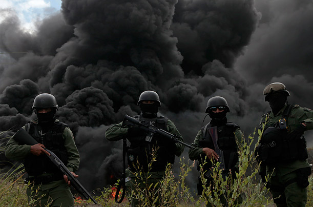 Panamanian Special Forces officers pose for a photo as a column of smoke rises from the burning of narcotics during a drug disposal operation in Panama City.