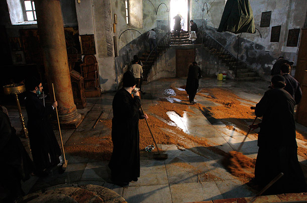 Greek Orthodox clergymen sweep the floor of the Church of the Nativity in the West Bank town of Bethlehem
