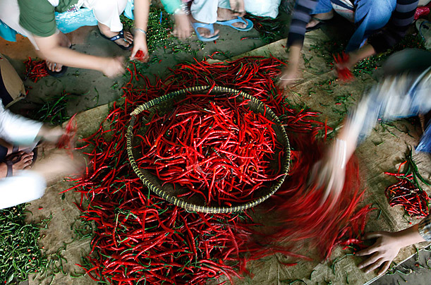 Workers select chilis at the Kramat Jati vegetable distribution center in Jakarta, Indonesia.