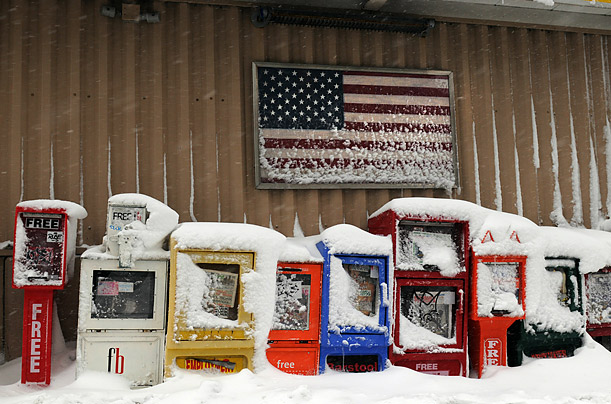 Snow sits atop newspaper boxes at a bus stop in Boston, MA.  A winter storm dropped over a foot of snow across New England.