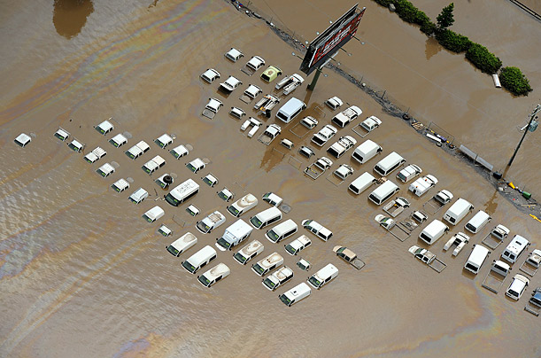 A car sales lot is submerged in waters as heavy rains continue to devastate much of Brisbane, Australia.