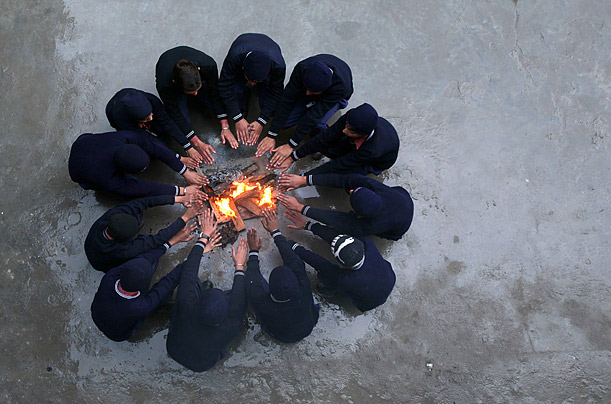 Children sit around a fire and warm themselves during their school's recess break in Jammu, India.