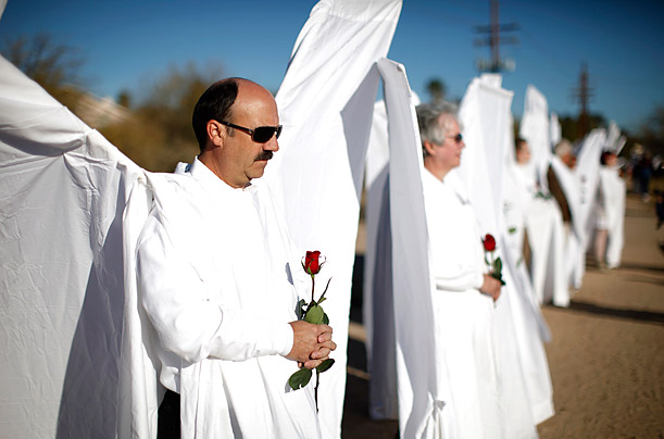 Men and women dressed as angels stand with roses outside the funeral Mass of federal judge John Roll, Tucson, Arizona.