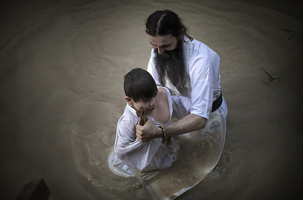 An eastern European Christian Orthodox priest baptizes a child in the Jordan river.