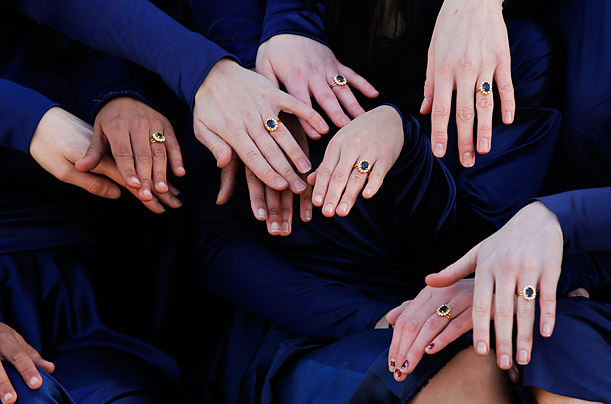 A group of students from the Royal College of Art pose wearing Kate Middleton style engagement outfits and rings they made themselves, outside Buckingham Palace in London.