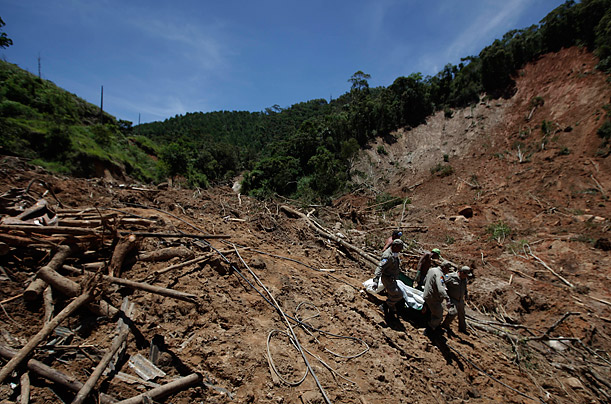 Firefighters, a National Force soldier and residents carry the body of a landslide victim from a home where eight family members were found dead in Nova Friburgo, Brazil. Deaths from last