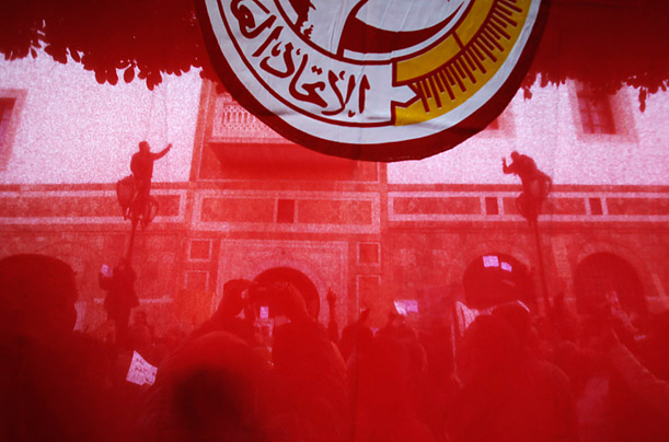 Tunisian protesters are photographed through a flag in front of the Prime Minister's office in downtown Tunis.