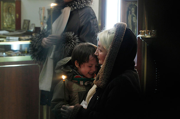 Family members of a victim grieve during a memorial service inside a church room at Domodedovo Airport, in Moscow.  A suicide bomber killed at least 35 people in an explosion on Monday.
