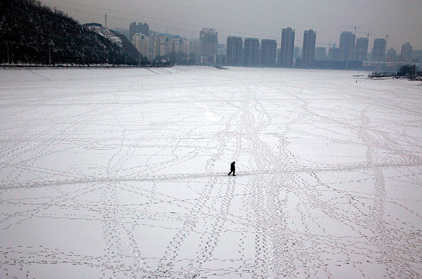 A man walks across a frozen river in China's northeastern Liaoning province.