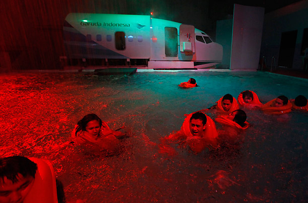 Indonesian flight attendants swim to safety during an aircraft emergency evacuation training in Jakarta.