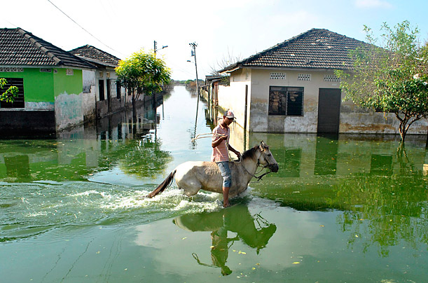 A person rides a horse in a flooded street after heavy rains caused damage to roads, crops, and animals in Manati, Colombia.