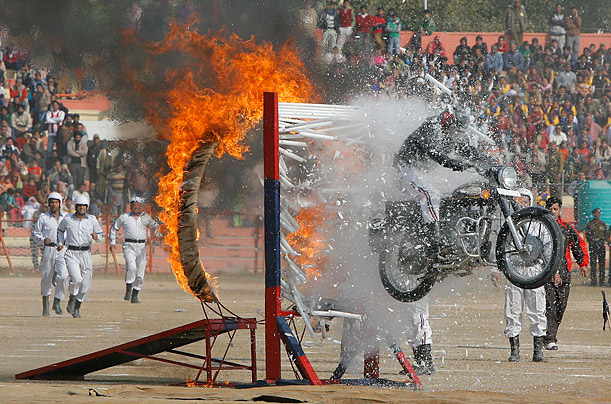 A policeman rides through a ring of fire and a wall of fluorescent  tube lights during Republic Day celebrations in Jammu, India.