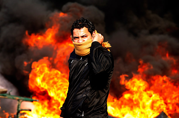 A protester stands in front of a burning barricade during a demonstration in Cairo, Egypt.