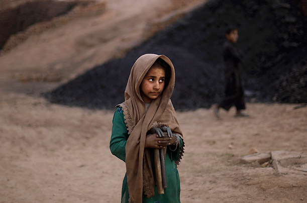 Pakistani Nooreen Hayat, 7, holds her tools after finishing her work of breaking coal in a brick factory for the day on the outskirts of Islamabad.