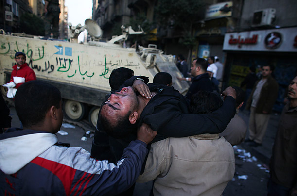 An injured anti-government protester is carried past an armored army vehicle during clashes in Tahrir Square, in Cairo.