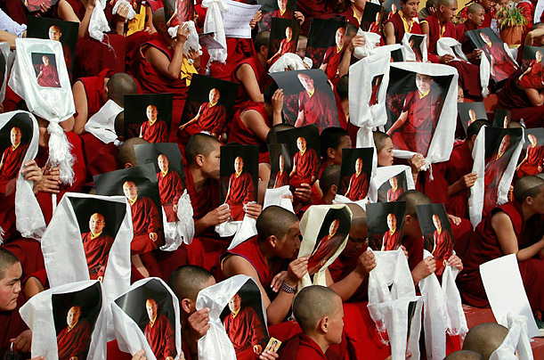 Tibetan Buddhist monks hold up portraits of the Karmapa during a gathering at the Gyuto Monastery in Dharamshala. Police recently discovered nearly $1 million at the monastery, the