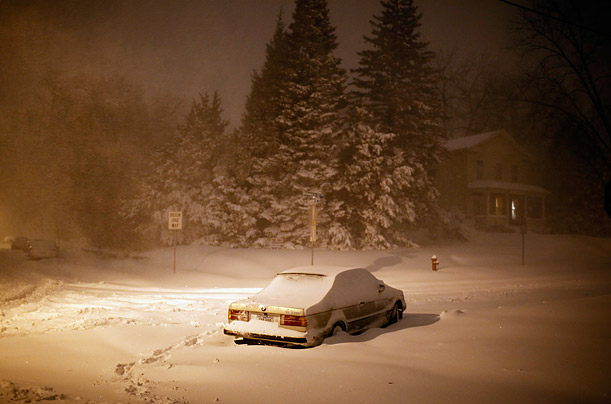 A car sits abandoned during a heavy snowfall in Iowa City, United States.
