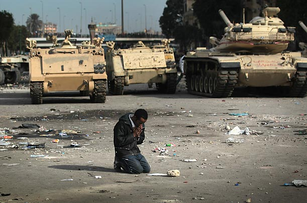 An anti-government demonstrator prays near Egyptian army vehicles in Cairo.