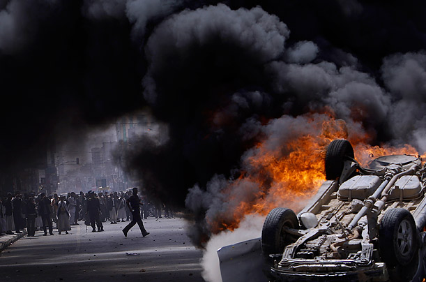 A vehicle burns on the streets of Sana'a, Yemen, as supporters of the government clash with antigovernment demonstrators.