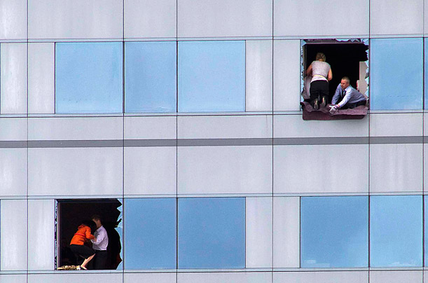 Office workers try to escape from a high-rise building in Christchurch, New Zealand, after an earthquake devastated the area, killing at least 65 people and injuring many others.