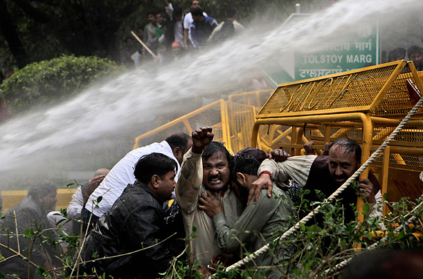 Activists from India's Bharatiya Janata Party shout as they take cover from a police water cannon during a protest in New Delhi.