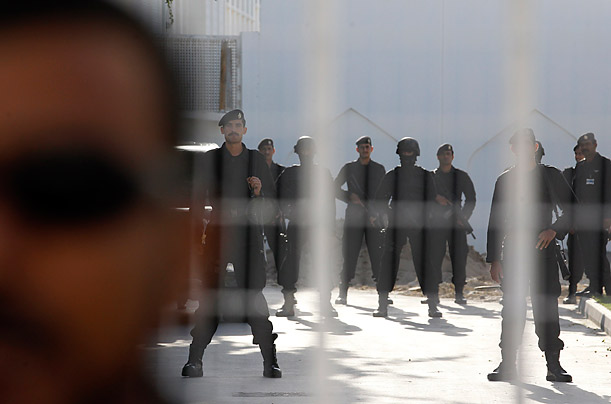 Bahraini special guards stand inside the Interior Ministry as thousands of protesters, calling for governmental change, demonstrate outside, in Manama.