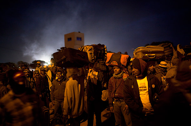 Workers from Bangladesh who fled the unrest in Libya hold their belongings while they wait for a bus in Ras Ajdir, Tunisia, on the Tunisia-Libya border.
