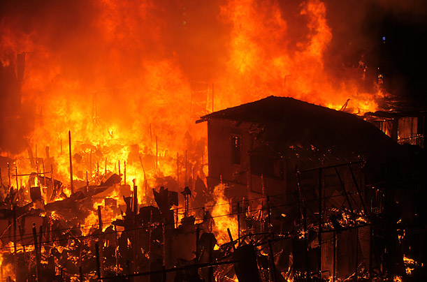 A hut is consumed by flames in a Mumbai slum. The neighborhood, near Bandra station in Mumbai's suburbs, is home to hundreds.