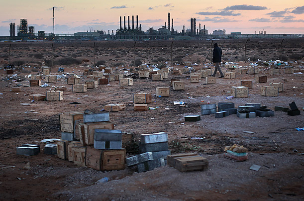 A Libyan rebel walks through a field of ammunition in Ras Lanuf, Libya.