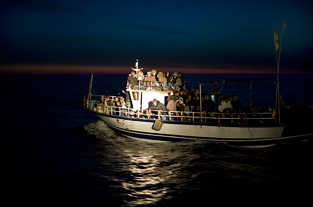 A boat of migrants sails by the Sicilian island of Lampedusa, in Italy.