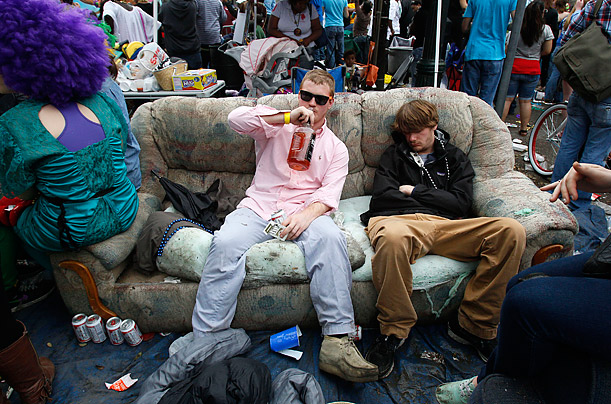A Mardi Gras reveler takes a sip of bourbon while sitting on a couch during the Zulu Social Aid and Pleasure Club parade in New Orleans.