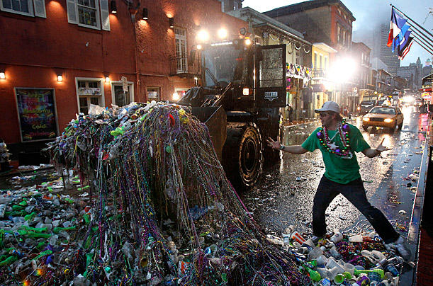 A front loader collects beads and other debris left behind by revelers during Mardi Gras on Bourbon Street in the French Quarter of New Orleans.
