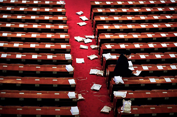 A worker arranges documents before the start of the Chinese People's Political Consultative Conference (CPPCC) plenary session in Beijing's Great Hall of the People.