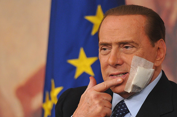 Italian Prime Minister Silvio Berlusconi reacts during a press conference in Rome three days after an operation to treat an injury sustained in attack by a deranged man in 2009.
